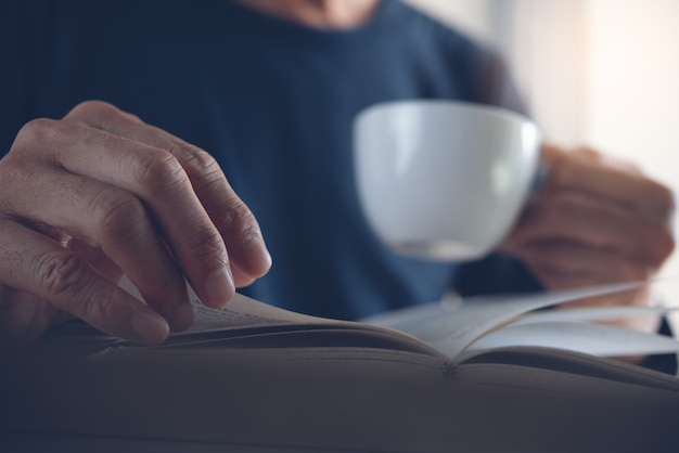 Close up of man reading book and drinking coffee at home