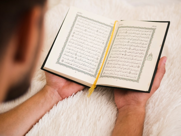 Close up of man reading from quran