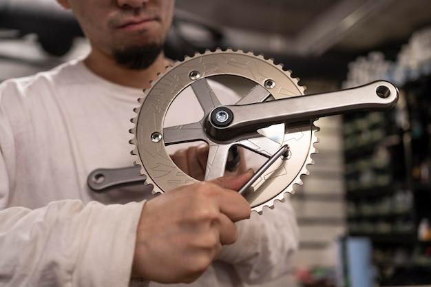 Крупным планом человек, ремонтирующий велосипед