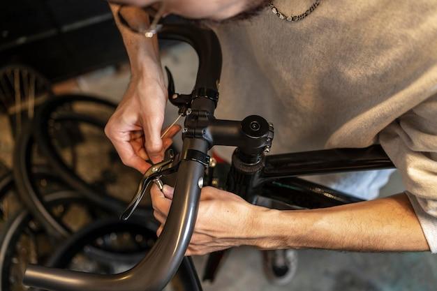 Close up man repairing bike at shop
