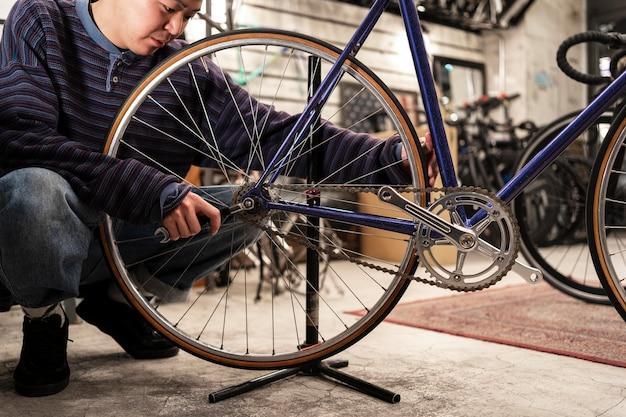 Крупным планом человек, ремонтирующий велосипед с гаечным ключом
