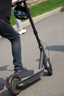 Close up of man riding black electric kick scooter lightweight and foldable modern transport