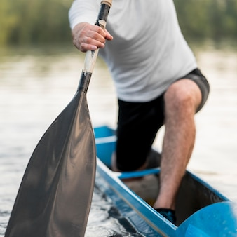 Close-up man rowing with oar