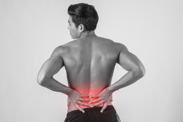 Close up of man rubbing his painful back isolated on white background.