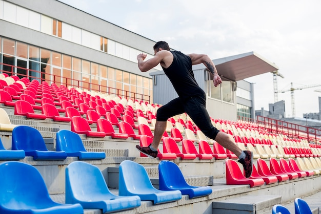 Close-up of man running up stairs on the stadium chairs