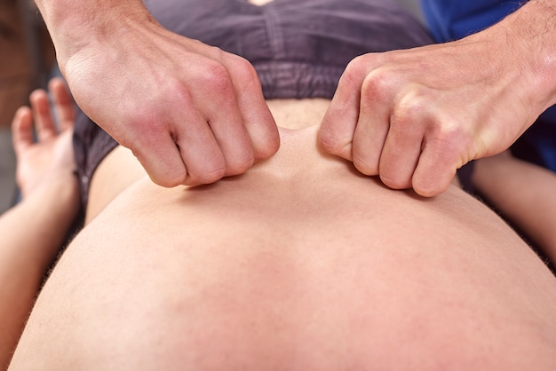 Close-up of man's back and hands of chiropractic