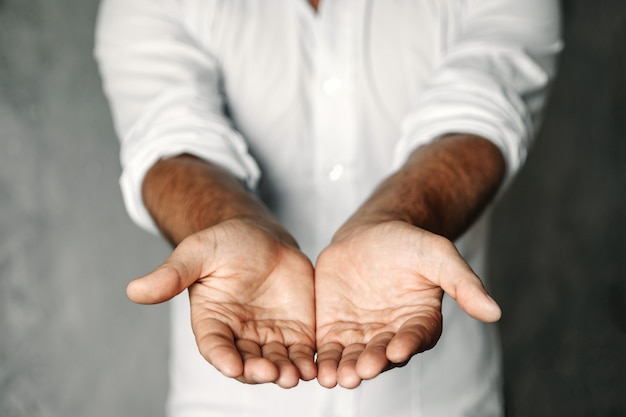 Close up of man's cupped hands show something on white