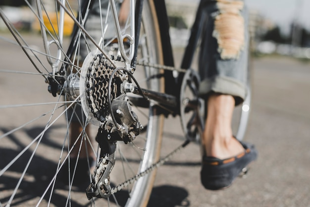 Close-up of man's feet on bicycle
