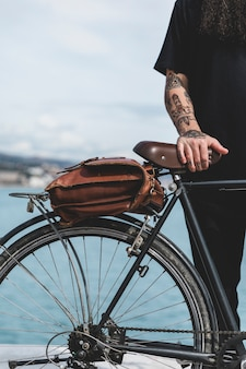 Close-up of man's hand on bicycle with brown bag