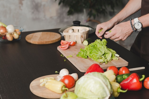 Close-up of man's hand cleaning lettuce on kitchen counter