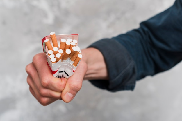 Close-up of man's hand crushing cigarettes box