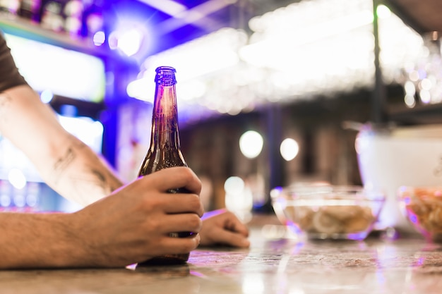 Close-up of man's hand holding beer bottle in the bar