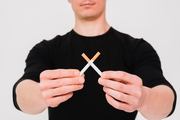 Close-up of man's hand holding crossed cigarettes over background