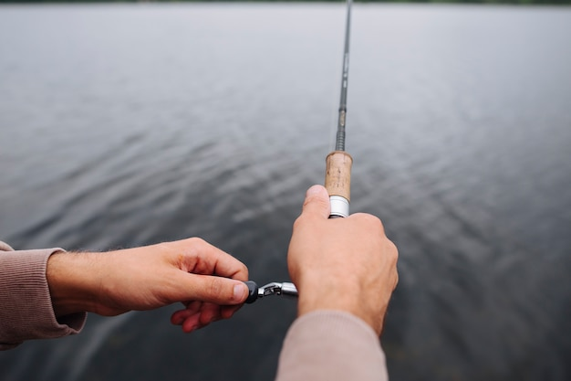 Close-up of man's hand holding fishing rod over the lake