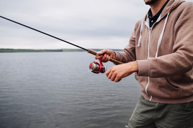 Close-up of man's hand holding fishing rod near the lake