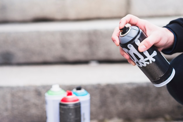 Close-up of a man's hand holding graffiti spray bottle