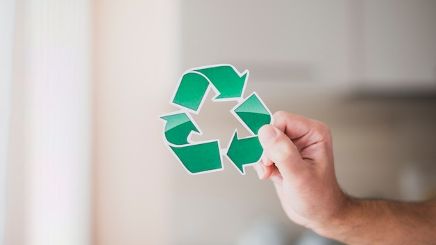 Close-up of man's hand holding green recycle icon