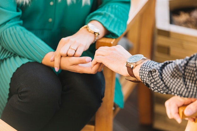 Close-up of man's hand holding his girlfriends hand sitting on chair