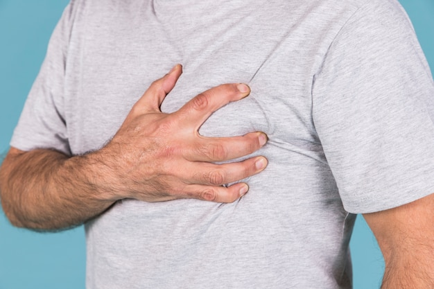 Close-up of a man's hand holding his heart in pain