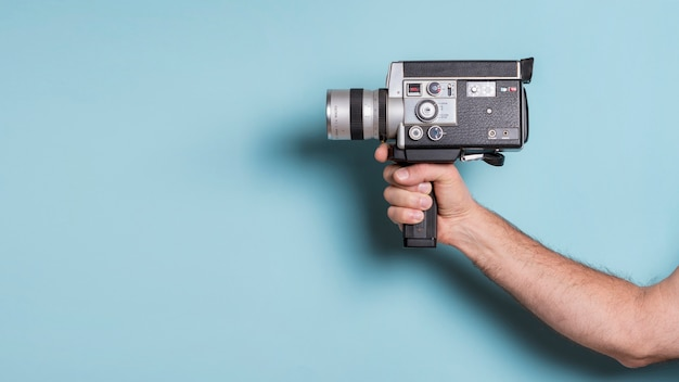 Close-up of man's hand holding old-fashioned camcorder against blue background