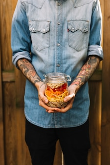 Close-up of a man's hand holding pasta salad in mason jar
