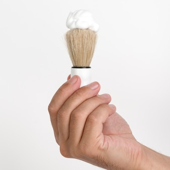 Close-up of man's hand holding shaving brush and foam against white wall