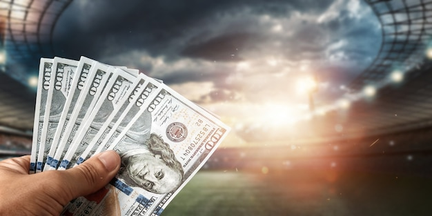 Close-up of a man's hand holding us dollars against the background of the stadium. the concept of sports betting, making a profit from betting, gambling. american football.
