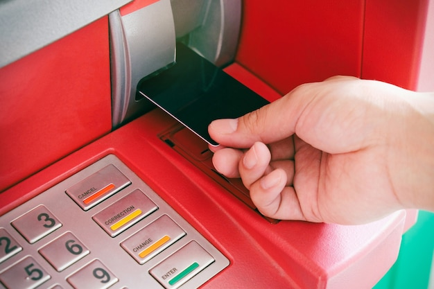 Close up of man's hand insert atm card into automated teller machine to withdraw cash mone