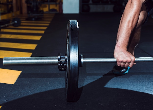 Close-up of a man's hand lifting barbell