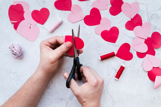 Close-up of man's hand making the heart shape garland on white textured backdrop