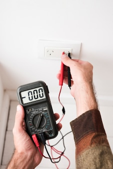 Close-up of man's hand plugging digital multimeter in plug at home