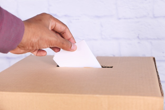 Close up of man's hand putting card in box with slot,