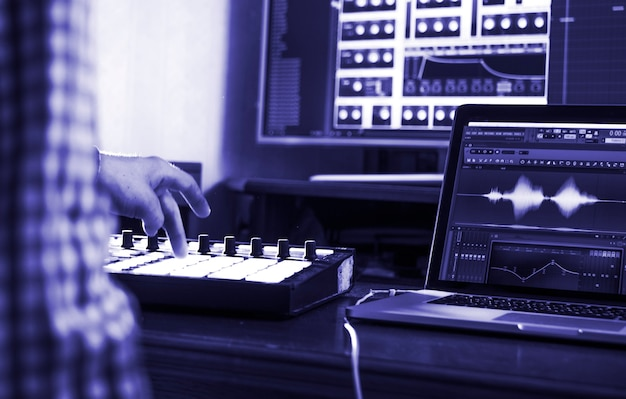 Close up man's hand recording sound in recording music studio color of the 2020 year trend, classic blue tones