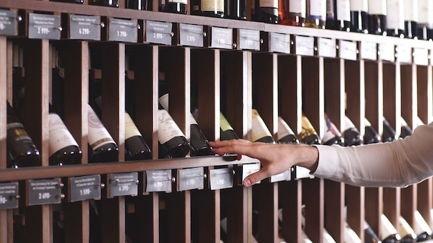 Close-up of a man's hand selecting a bottle of wine from a shelf in a store