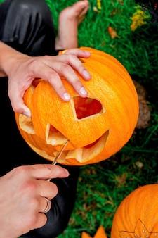 A close up of man's hand who cuts with knife a pumpkin as he prepares a jack-o-lantern. halloween.