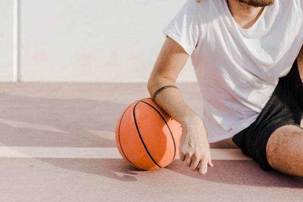 Close-up of a man's hand with basketball in court