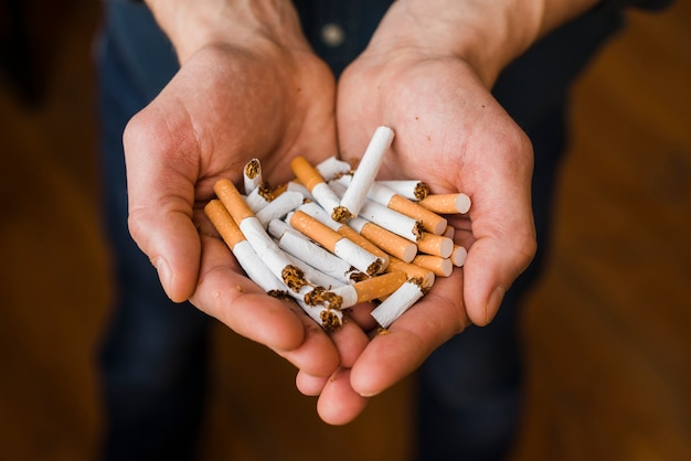 Close-up of man's hand with bunch of breaking cigarette
