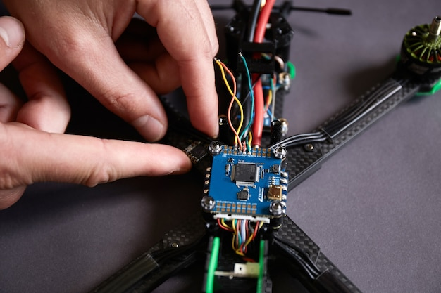 Close up of man's hands assembling a drone from parts, using tools, preparing high-speed racing quadcopter for flight. repair drone before training process.
