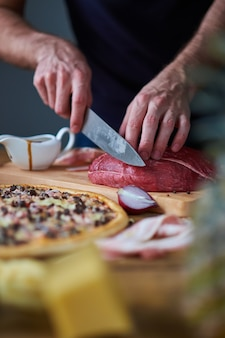 Close-up of man's hands cut beef with knife on board. sauce-boat, half onion and cooked pizza lying on table too.