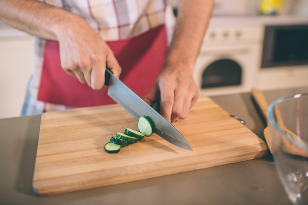 Close up of man's hands holding knife and cutting cucumber into pieces. he does it on desk. there is a glass bowl at table. guy wears pron.