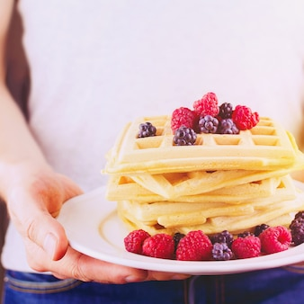Close up of man's hands holding waffles with berries and cup of coffee. concept of breakfast in bed. selective focus