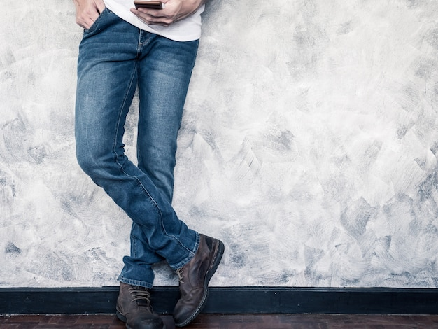 Close up of man's legs in jeans and boots on wooden floor.