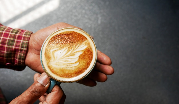 Close up of man serving coffee in coffee shop.