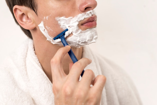 Close up man shaving cheek