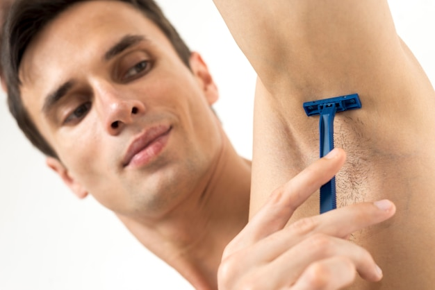Close up man shaving his armpit