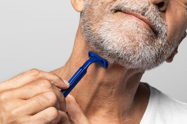 Close-up man shaving his neck