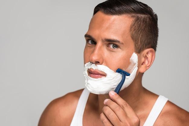 Close-up man shaving with razor