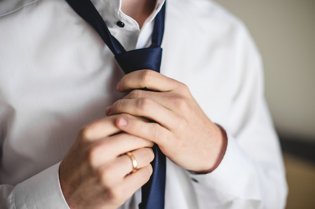 Close up of man in shirt dressing up and adjusting tie on neck at home.