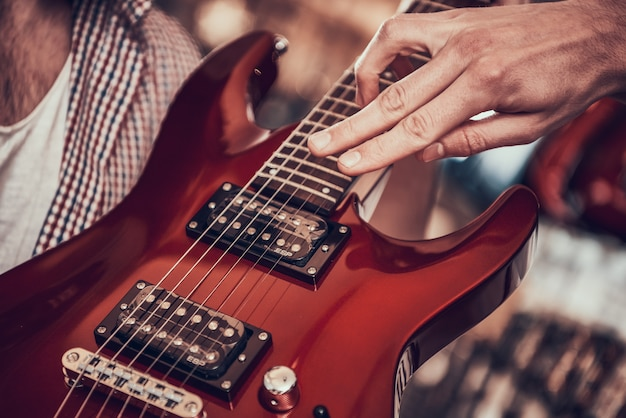 Close up. man shows customer on strings of electric guitar
