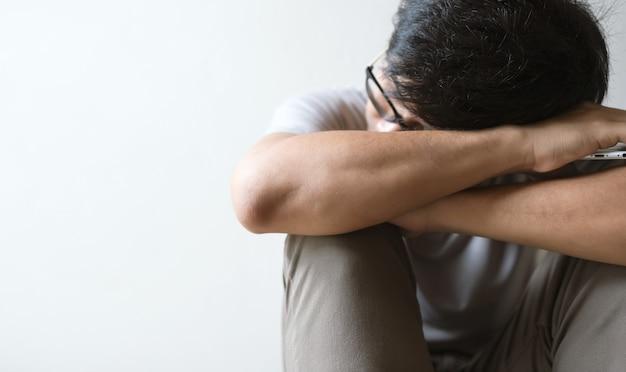 Крупным планом человек сидит в одиночестве валит грустный